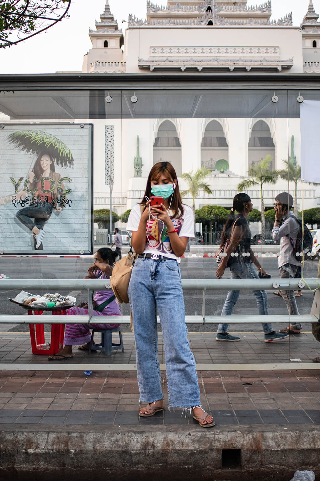 Woman in face mask uses mobile phone in Yangon, Myanmar, in 2020. China has provided substantial COVID-19-related aid to Myanmar.