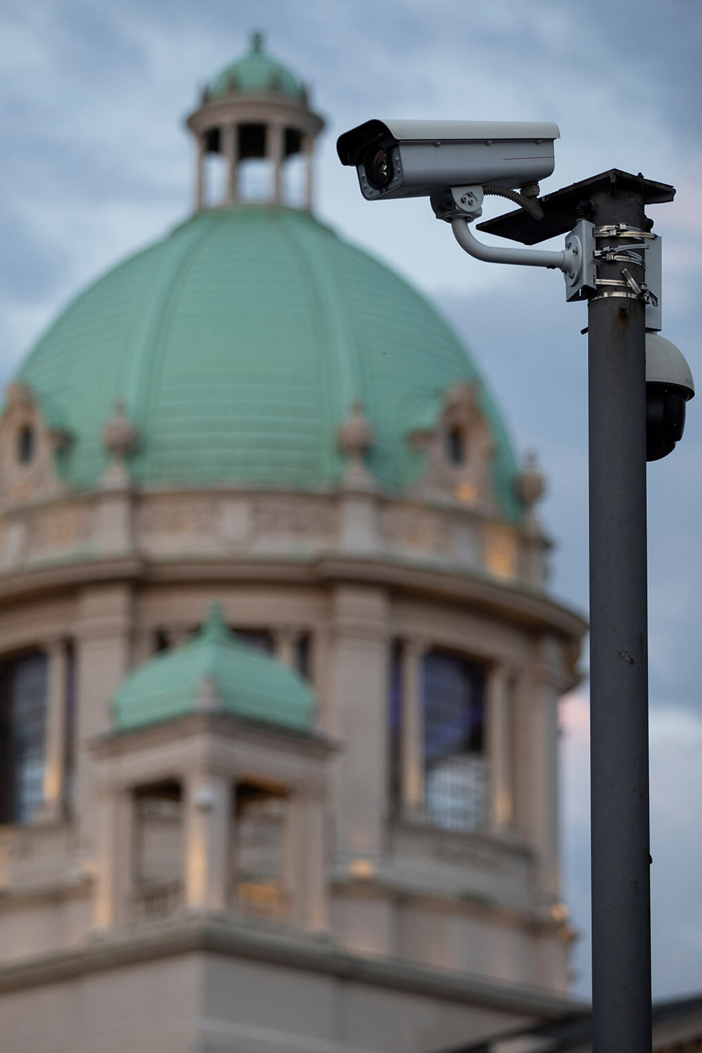 Surveillance camera stands in front of Serbia's parliament building in Belgrade, in 2020. Chinese firms have helped Serbia implement a surveillance camera program.