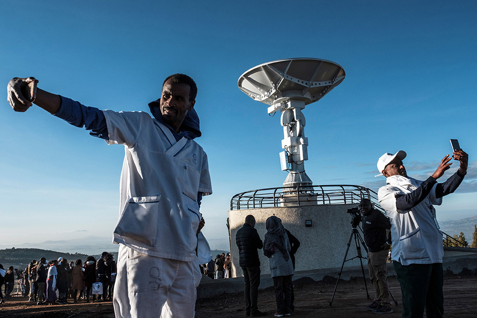 People take selfies in front of Ethiopian satellite antenna during ceremony for the Ethiopian Remote Sensing Satellite, which was launched by China.