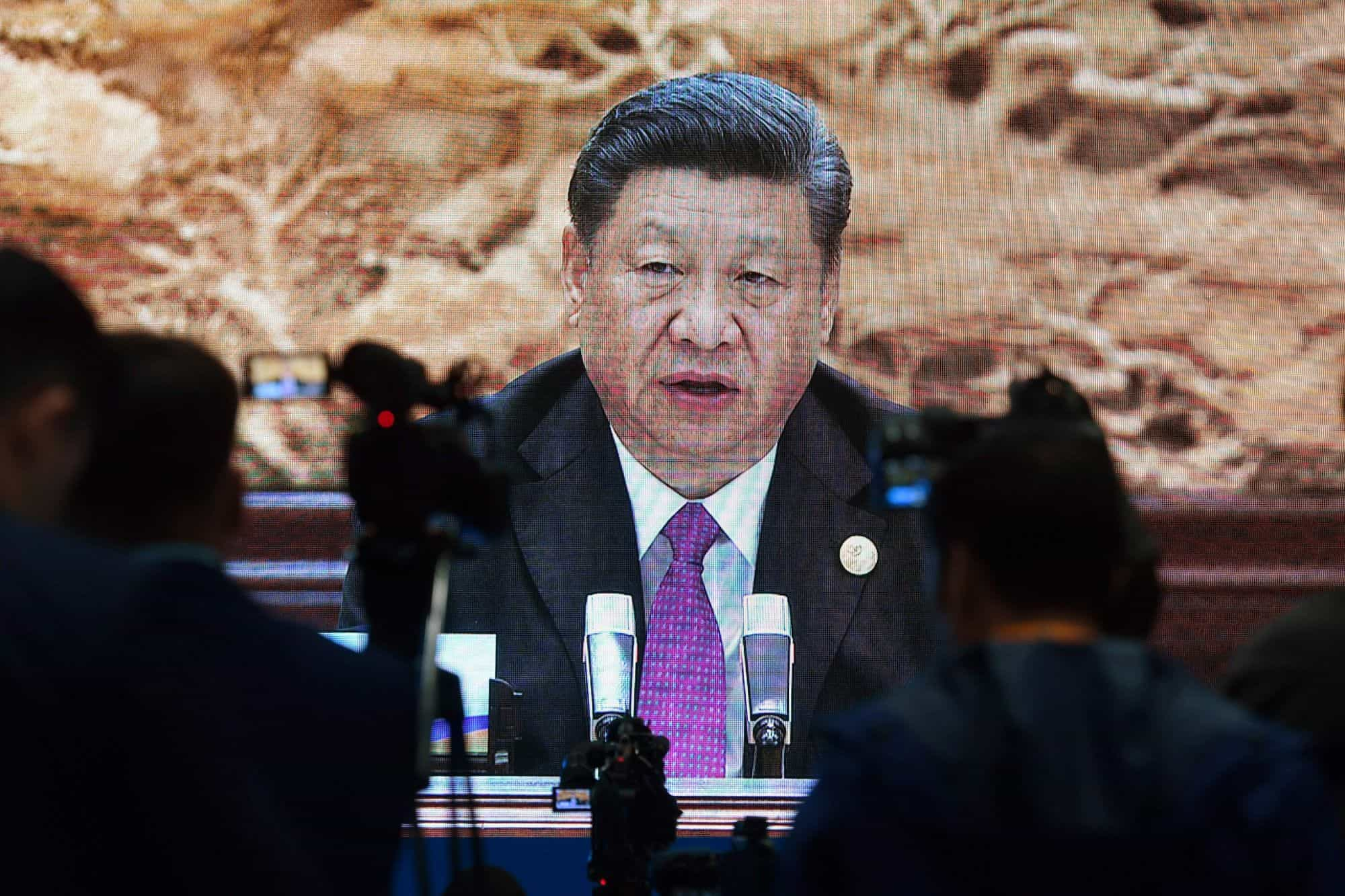 Journalists watch an image of Chinese President Xi Jinping speaking at the Belt and Road Forum in Beijing in April 2019.