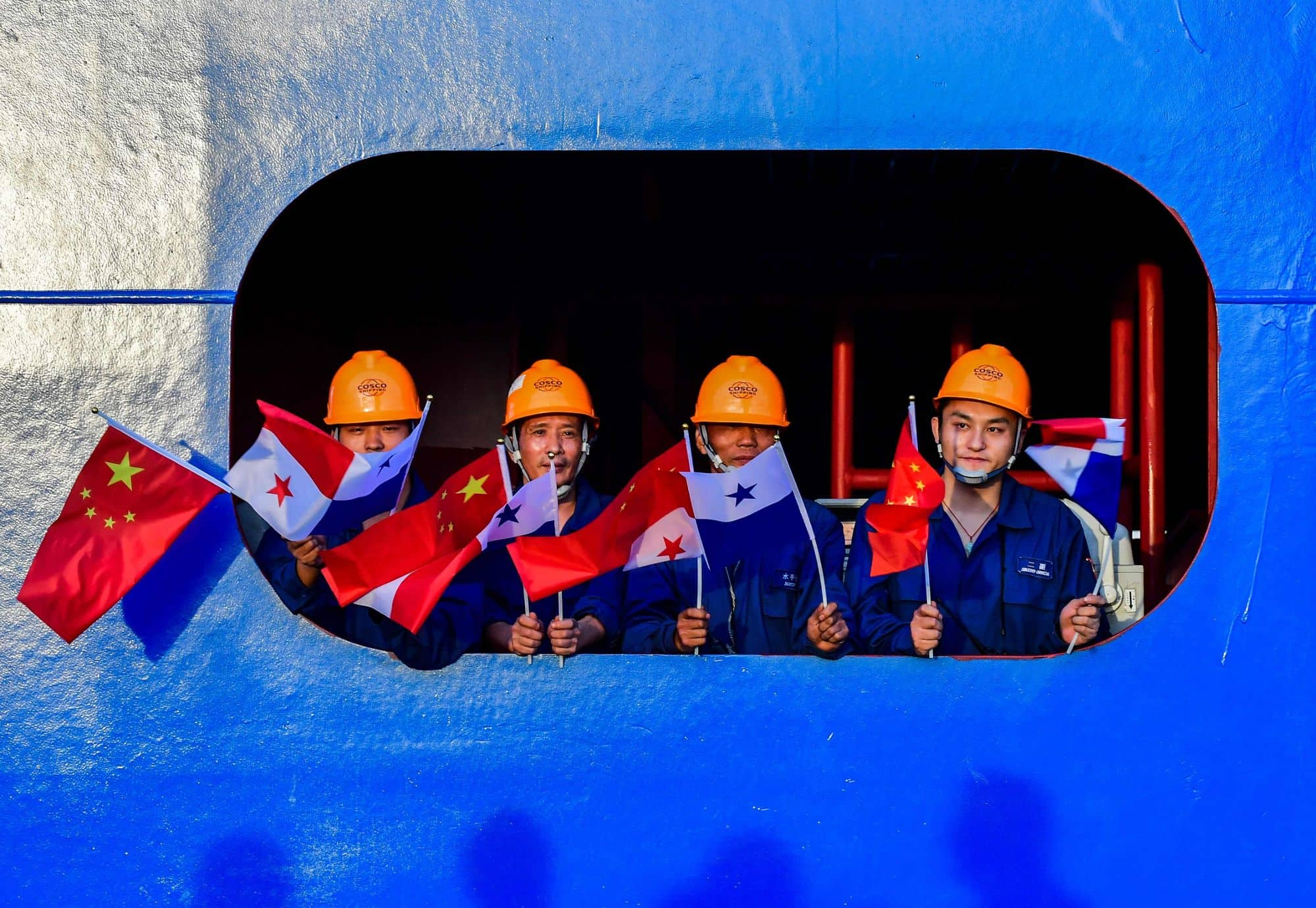 Crew members of a Chinese container ship wave Chinese and Panamanian flags during an official visit by Chinese President Xi Jinping to the country in December 2018.