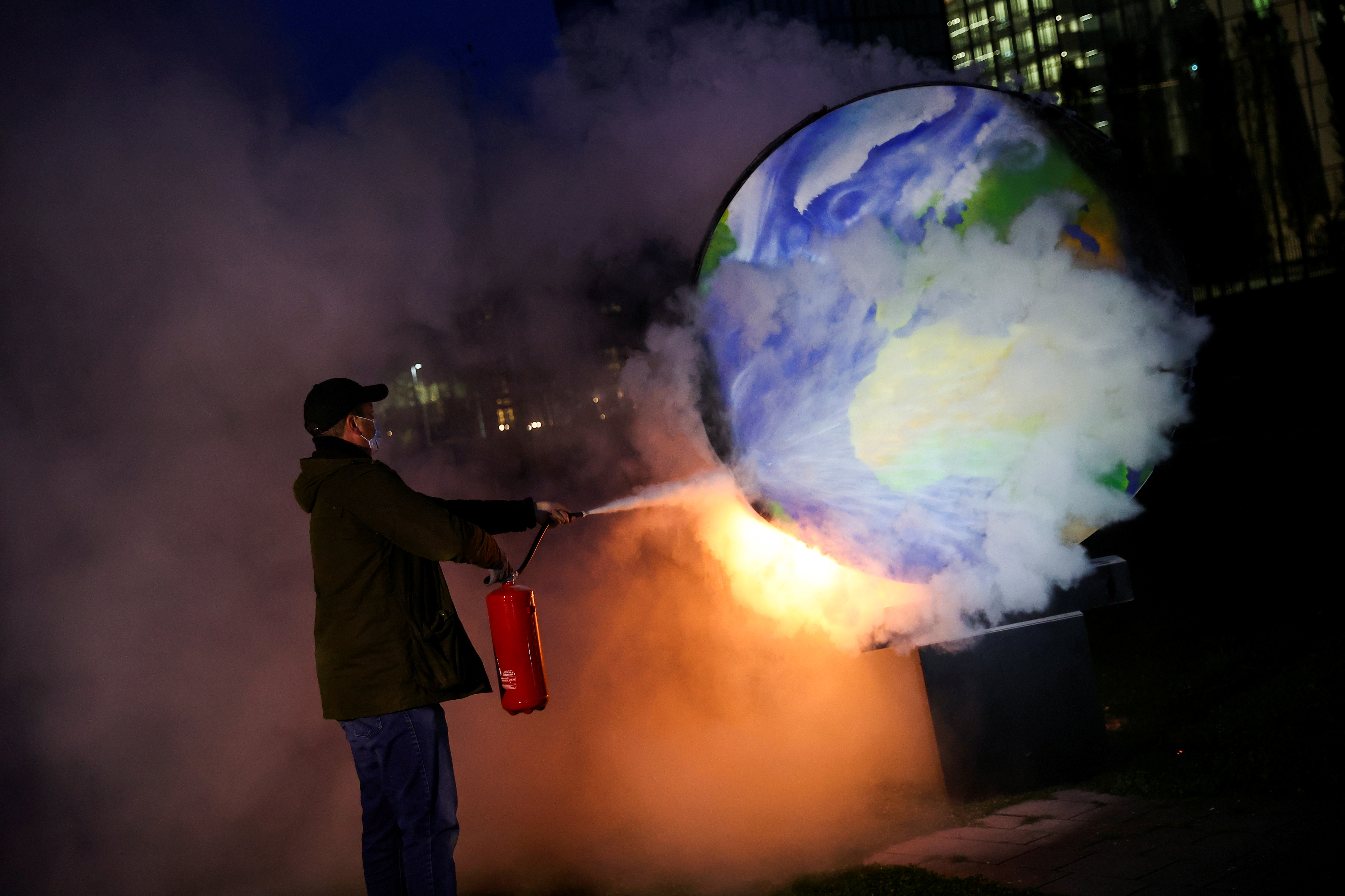 A person uses an extinguisher toward a burning paper-made globe during a demonstration against the fossil fuel industry in Frankfurt, Germany on October 21, 2020.