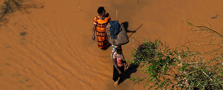 People wade across a flooded plain