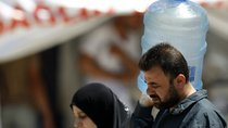 A Syrian man carries a water container as he is accompanied by a woman at a refugee camp in the Turkish border town of Yayladagi (Reuters/Umit Bektas)