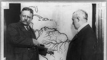 President Roosevelt pointing at a map of South America towards the area explored during the Roosevelt-Rondon Scientific Expedition in Brazil as another man looks on.