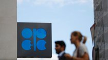 Two persons pass the logo of the Organization of the Petroleoum Exporting Countries (OPEC) in front of OPEC's headquarters in Vienna, Austria June 19, 2018.