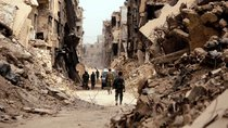 Soldiers walk past damaged buildings in Damascus