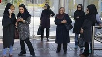 Women wait for a bus in central Tehran, Iran.