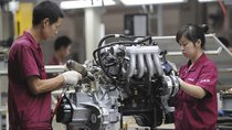 Employees assemble an engine at the production line of an automobile company in Anhui province, China. July 16, 2009.