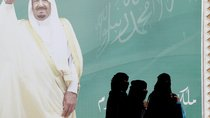Women walk past a poster of Saudi Arabia's King Salman bin Abdulaziz Al Saud.
