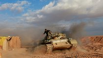 PMF fighters ride a tank in Iraq.