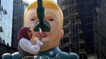 A woman stands next to an inflatable tank with U.S. President Donald Trump outside an art exhibition 'MonuMental' by the pseudonymous artist, Saint Hoax in downtown Beirut, Lebanon October 12, 2018.