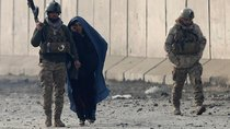 Afghan security forces escort a woman at the site of a car bomb blast in Kabul, Afghanistan January 15, 2019.