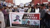 "Protesters hold a sign that says ""Free Zakzaky"" and has images of the Nigerian Shia leader."