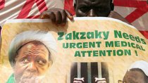 "A protester holds a banner that reads, ""Zakzaky needs urgent medical attention!"""