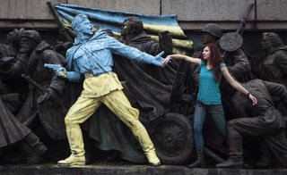 A woman holds hands with a statue painted in Ukrainian colors