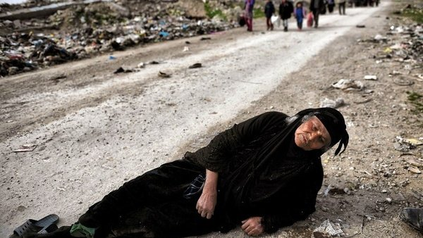 An Iraqi woman lies on the ground as civilians flee Mosul while Iraqi forces advance inside the city during fighting against the so-called Islamic State group's fighters on March 8, 2017.ARIS MESSINIS/AFP/Getty Images