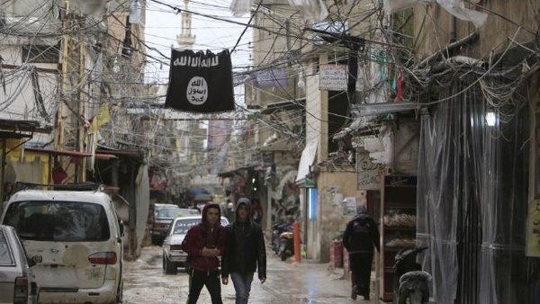 Youth walk under an Islamic State flag in Ain al-Hilweh Palestinian refugee camp (Ali Hashisho/Reuters).
