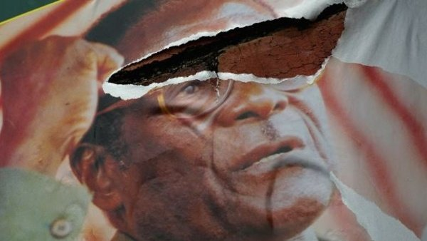 A poster of President Robert Mugabe hangs torn on a streetside wall in Bulawayo, Zimbabwe. John Moore/Getty Images